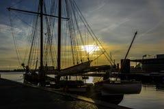 Шлюпка Sailing на заходе солнца Стоковые Изображения