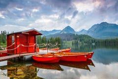 Шлюпки забытьё, спокойное озеро, фантастические горы и flo облаков Стоковые Фото