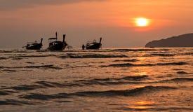 3 шлюпки длинного хвоста плавая во время захода солнца Стоковое Изображение