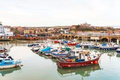 Шлюпки и корабли причалили в малом порте, на заднем плане камне Стоковые Изображения