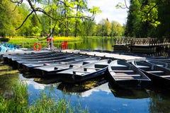 Шлюпки на пристани в городе паркуют Парк лета с озером Состыкованная деревянная весельная лодка Стоковая Фотография