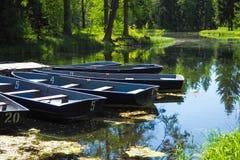 Шлюпки на пристани в городе паркуют Парк лета с озером Состыкованная деревянная весельная лодка Стоковая Фотография RF