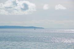 Шлюпки плавая в расстоянии на яркий солнечный день Стоковые Изображения