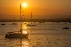 шлюпки плавая заход солнца Стоковые Фотографии RF