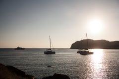 Шлюпки плавая на заход солнца Стоковые Фотографии RF