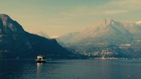 Шлюпки плавая через озеро горы озеро Италии como стоковые изображения rf
