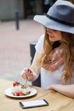 Шляпа женщины нося есть brakfast на таблице Стоковые Фото