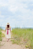 Шляпа женщины нося идя на путь пляжа Стоковая Фотография