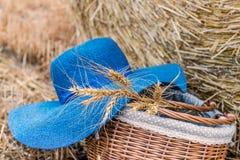 Шляпа и корзина женщин на стоге сена Стоковые Изображения RF