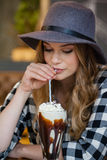 Шляпа молодой женщины нося выпивая холодный кофе Стоковое Фото