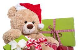 Шляпа рождества плюшевого медвежонка нося с подарками на белой предпосылке Стоковые Изображения RF