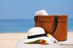 Шляпа, сумка, стекла солнца и полотенце на тропическом пляже стоковые изображения rf