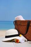 Шляпа, сумка, стекла солнца и полотенце на тропическом пляже стоковая фотография rf