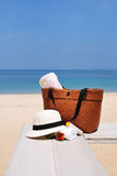 Шляпа, сумка, стекла солнца и полотенце на тропическом пляже стоковое фото