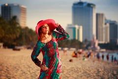 шляпа тонкой девушки внутри длинная и большая на пляже против моря города Стоковая Фотография