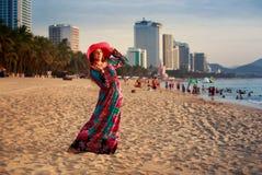 шляпа тонкой девушки внутри длинная и большая на пляже против моря города Стоковые Изображения