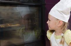 Шляпа шеф-повара девушки нося смотря в печь на еде Стоковое Изображение