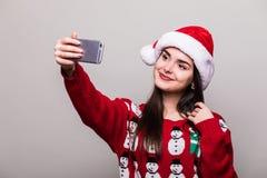 Шляпа santa носки модели девушки и свитер рождества принимают selfie Стоковые Фотографии RF