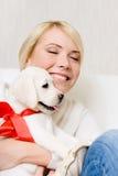 Щенок обнимать labrador женщины с красной лентой Стоковая Фотография RF