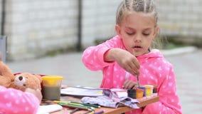 Щетка данков семилетней девушки трудная в опарнике с чертежом на альбоме, усаживанием краски акварели на таблице с другой девушко сток-видео