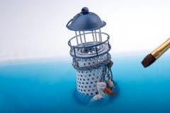 Щетка картины и меньший модельный маяк в воде Стоковые Фото