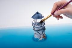 Щетка картины и меньший модельный маяк в воде Стоковые Изображения