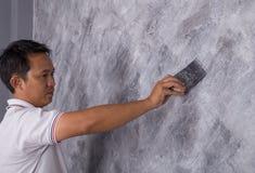 Щетка пользы работника для стиля просторной квартиры краски цвета конкретного на стене Стоковое фото RF