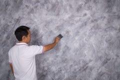 Щетка пользы работника для стиля просторной квартиры краски цвета конкретного на стене Стоковое Изображение RF