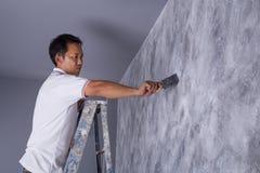 Щетка пользы работника для стиля просторной квартиры краски цвета конкретного на стене Стоковые Изображения RF