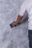 Щетка пользы работника для стиля просторной квартиры краски цвета конкретного на стене Стоковые Фотографии RF