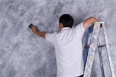Щетка пользы работника для стиля просторной квартиры краски цвета конкретного на стене Стоковое Фото