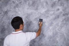 Щетка пользы работника для стиля просторной квартиры краски цвета конкретного на стене Стоковая Фотография RF