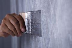 Щетка пользы работника для стиля просторной квартиры краски цвета конкретного на стене Стоковая Фотография