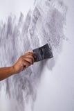 Щетка пользы руки для стиля просторной квартиры краски цвета конкретного на стене Стоковое фото RF