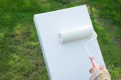 Щетка ролика краски покрашена белый на поле цемента Стоковая Фотография