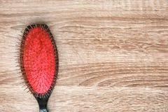 Щетка с потерянными волосами на деревянной предпосылке стоковое фото