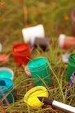 Щетка с чонсервными банками гуаши на траве Внешняя картина с красками и щеткой Стоковое Изображение
