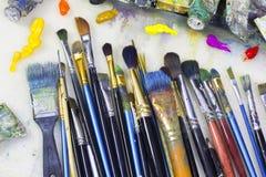 Щетки для красить и покрашенные краски масла лежат на палитре Стоковые Изображения