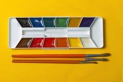 Щетки и акварели на желтой предпосылке Стоковая Фотография