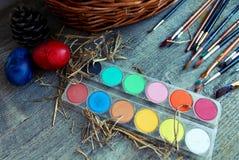 Щетки, краски и пасхальные яйца на tableb Стоковое Изображение