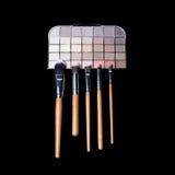 Щетки состава и красочная палитра теней глаза состава на черной предпосылке Натюрморт женщины моды Стоковая Фотография