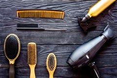 Щетки, фен для волос и спрей для волос гребня на сером деревянном взгляд сверху предпосылки Стоковое Фото