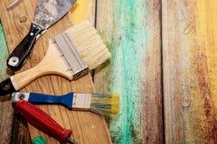 Щетки, шпатель и отвертки на покрашенной покрашенной деревянной предпосылке Стоковое фото RF
