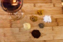 Щипки трав и специй на разделочной доске с стеклом красного вина Стоковое Изображение RF