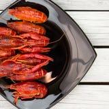 Ые Crawfish woden предпосылка Деревенский тип Красный цвет закипел раков на черной прямоугольной плите стоковые фото