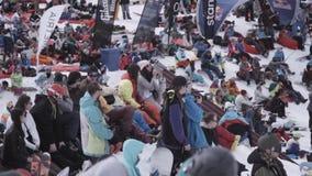 лыжа курорта Snowboarders и лыжники наблюдая что-то внутри располагаются смелости сток-видео