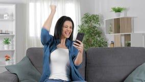 Эйфоричная женщина проверяя телефон празднуя успех видеоматериал