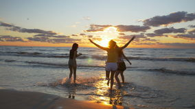 Эйфоричные девушки бежать к морю и получая их ноги в воду сток-видео