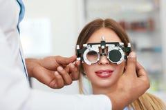Экзамен глаза Женщина в стеклах проверяя зрение на клинике стоковое изображение