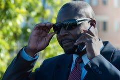 Экзекьютив на солнечных очках сотового телефона нося Стоковое Изображение RF